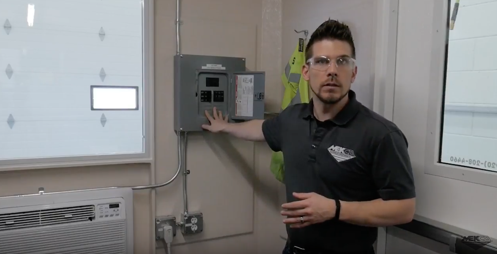 Adam in front of the 100 AMP electrical panel inside the onsite system