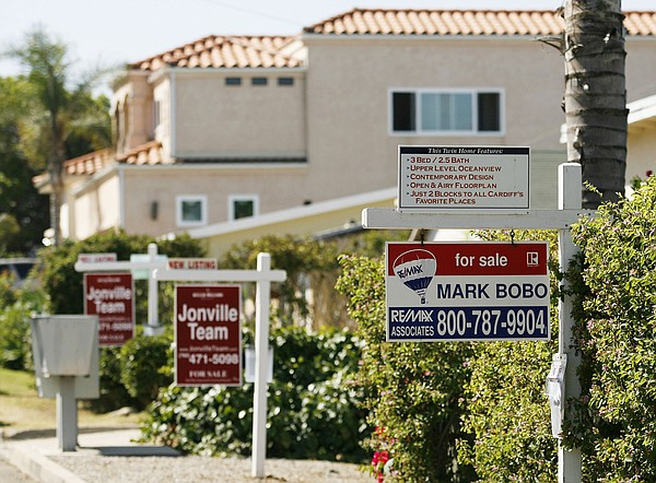 Real estate signs advertise the sale of three houses in a row in Encinitas in San Diego County, July 13, 2006.(Associated Press)