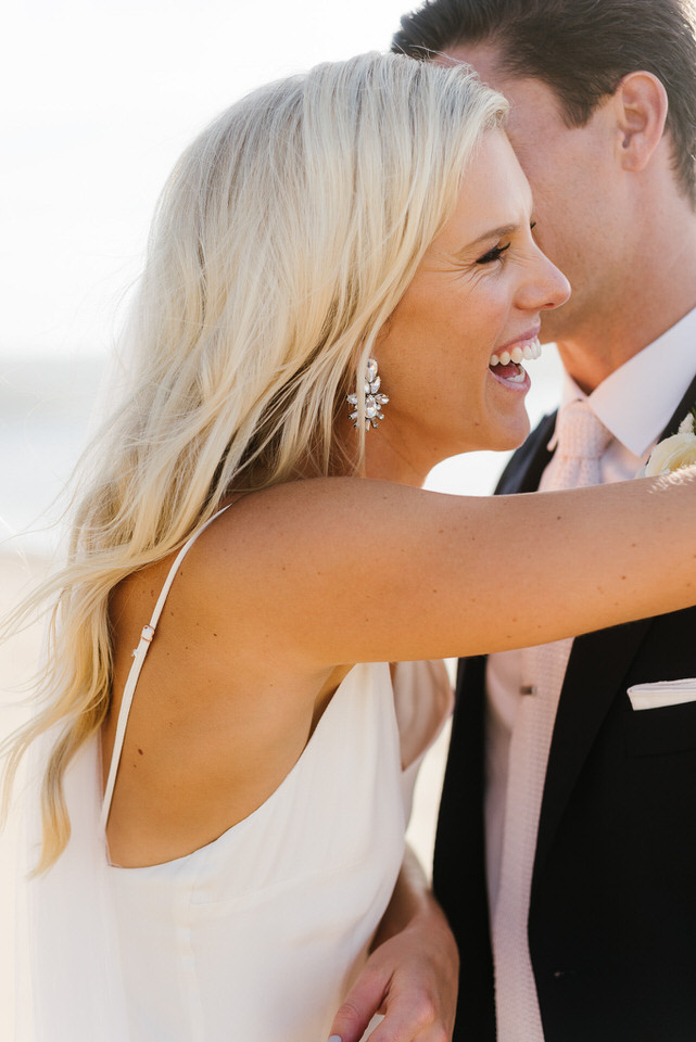 Bride looks radiant laughing with her groom on the beach at Palm beach