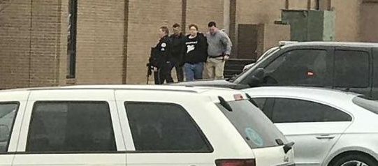 Police escort a young man out of Marshall County High School after a gunman opened fire on students killing 2 and injuring 19. (Dominico Caporali via AP)