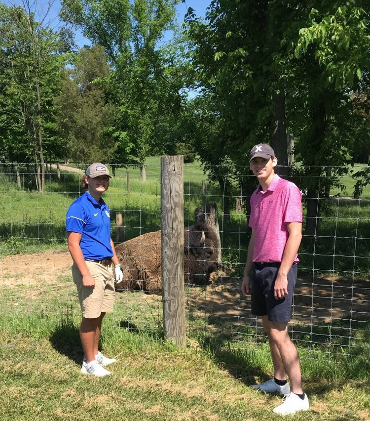 Carter Kurz and Michael Shipp pose in front of the pet buffalo on the first hole at Stonelick Hills.