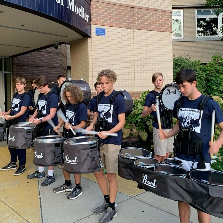 Joseph Meehan (center) and the rest of the Moeller drumline perform outside the main entrance on Fridays  by MoeMNDBand Instagram