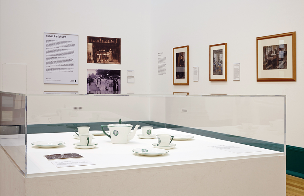 This image shows Sylvia Pankhurst's angel of freedom motif adorning a tea service that the WSPU sold to raise funds for their campaign, in the background are three paintings from the 1907 'Women Workers of England' series which were created to accompany her article under the same title publicising the harsh conditions and unequal pay that women faced in various industries.