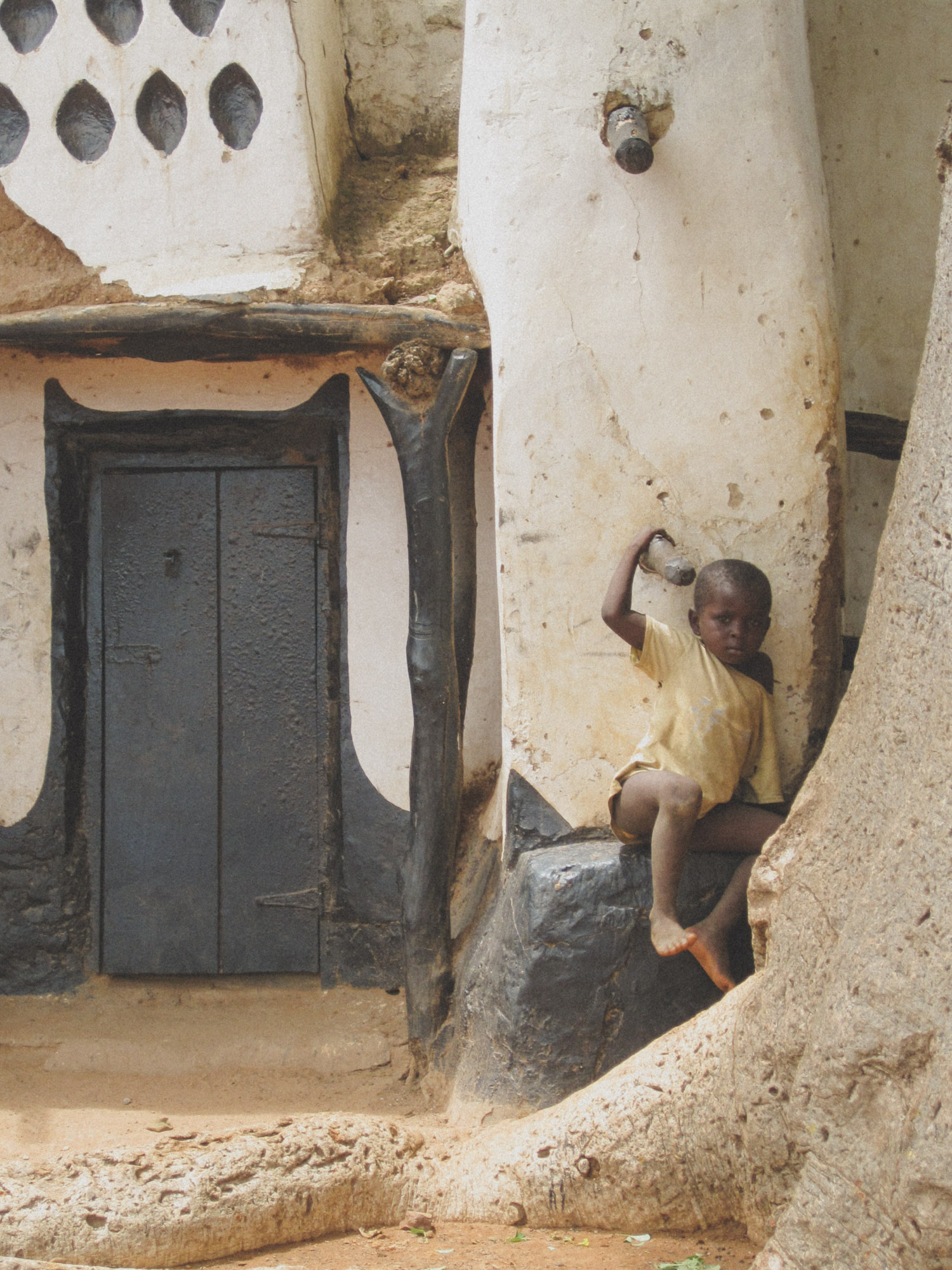 A child outside Larabanga mosque, one of the oldest mosques in Western Africa | Photo by Caroline Taft,  The Brazen Gourmand