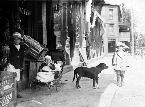 """Children wait patiently with their dog """"Spot"""" on the sidewalk outside Hobart Edwards's Grocery Store at 105 West Liberty Street while their """"Mom"""" shops for the family daily supply of food in 1912"""