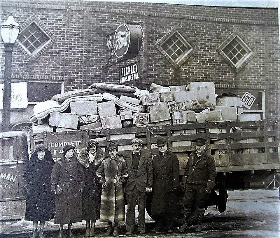 Frank Feckley, second from the right and Robert O. Bowman third from the right, Medina proprietors team up to collect goods for the poor during the depression days of the late 1930's.