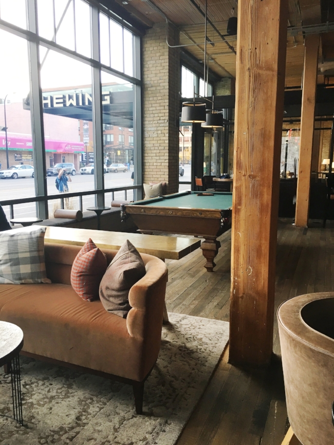 A pool table, cushy velvet sofas, and rustic beams
