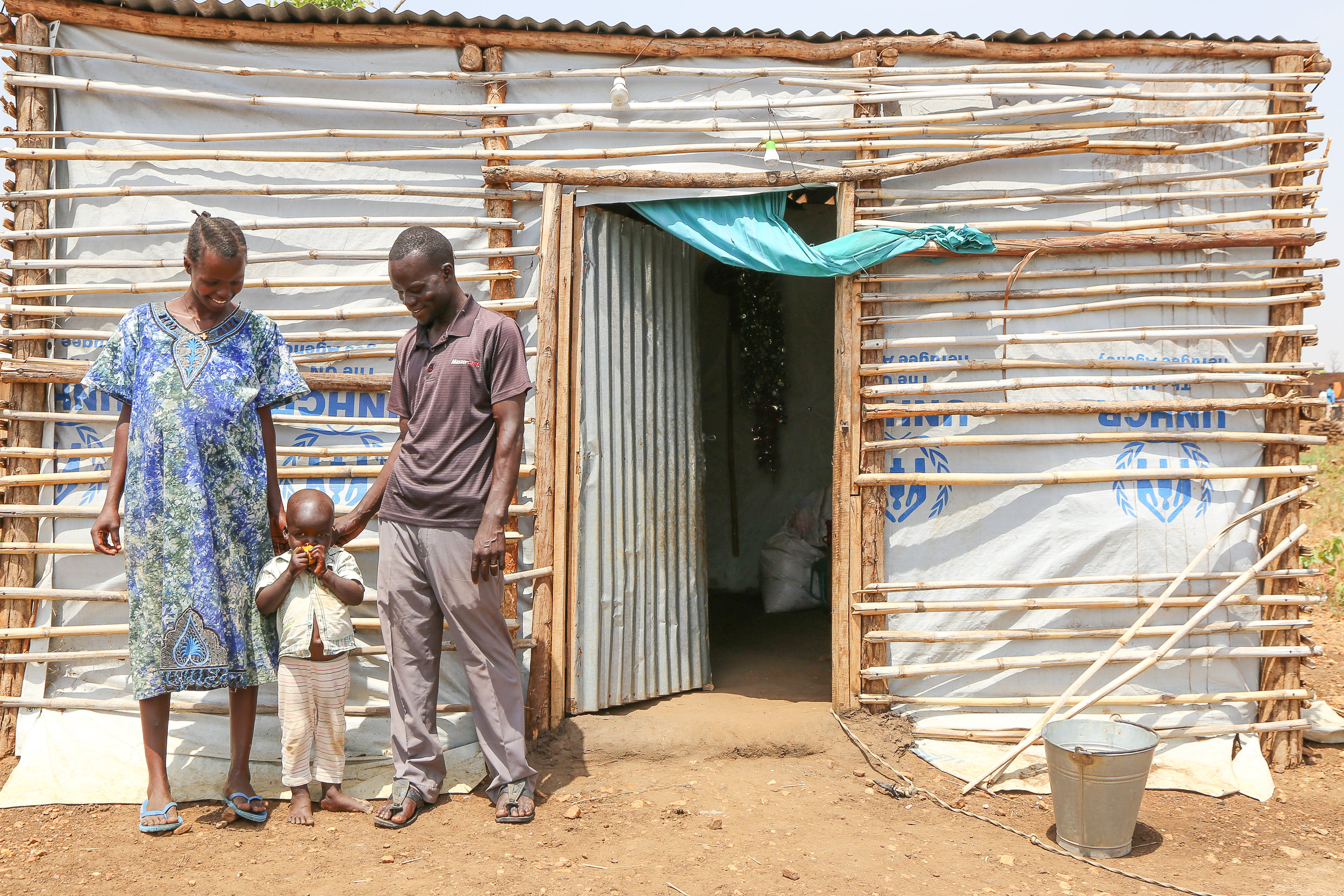 Issa & His Family outside their home in Pagirinya Refugee Settlement, Adjumani District