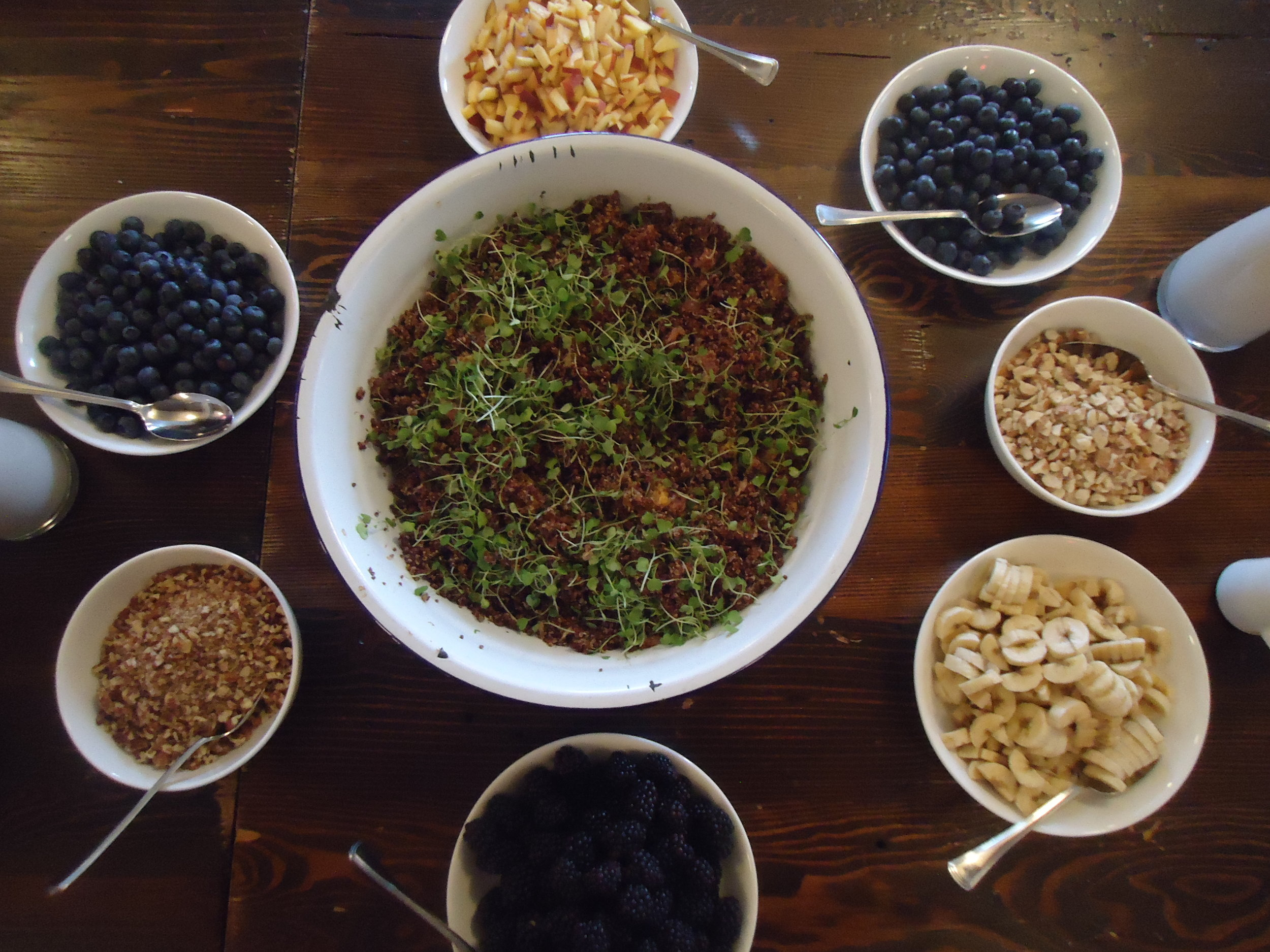 Citrus quinoa surrounded by berries, peaches, bananas, nuts and almond milk; by Chef Foulois.
