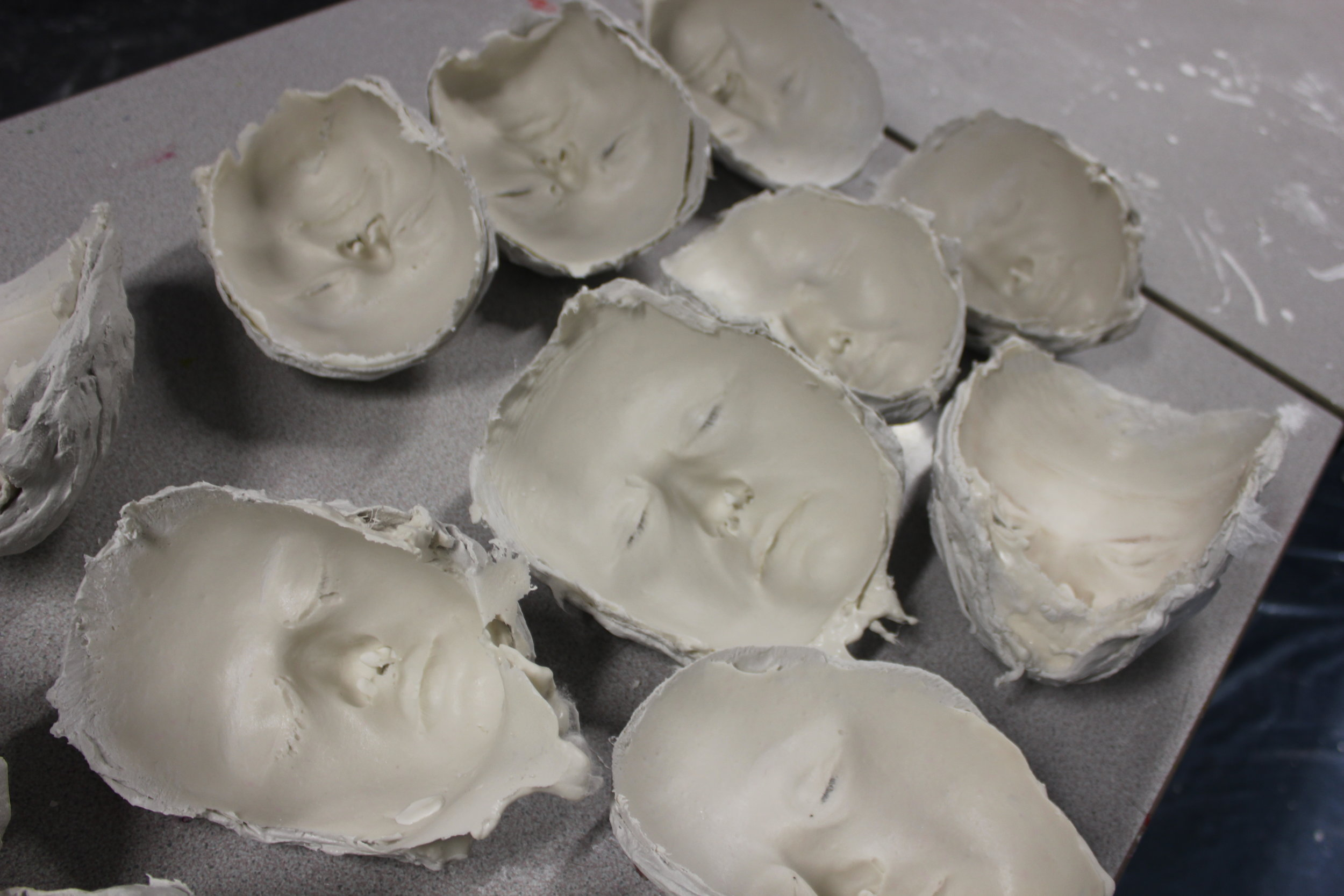 Multiple moulds waiting to be filled with plaster, from group face casting workshop at Invicta Grammar School for Girls, Kent.