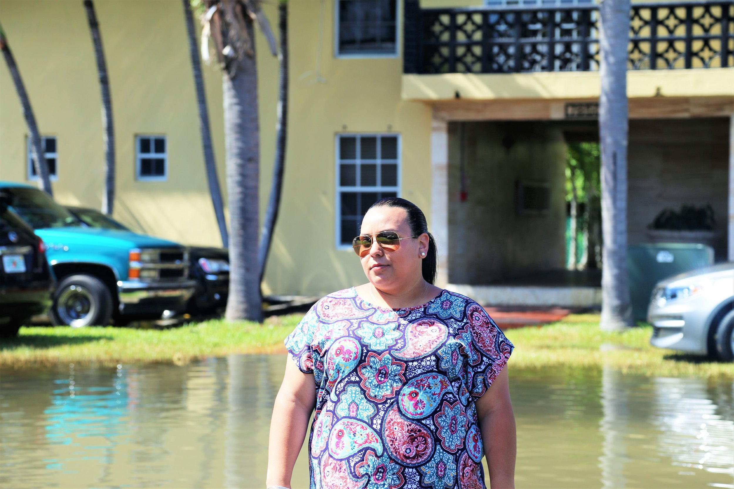 Karina during king tides in October of 2016 outside an apartment building in the community of Shorecrest, Miami. Photo: Dayna Reggero, Climate Listening Project.