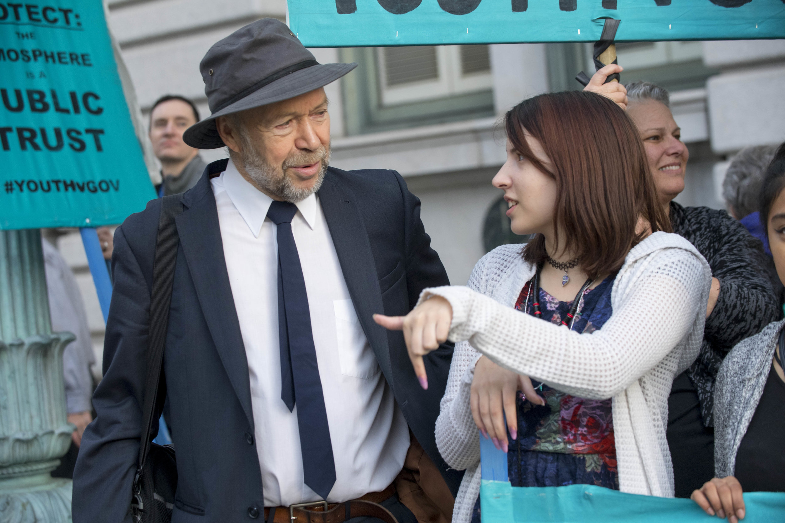Jayden (right) with Dr. James Hansen (left) outside the 9th Circuit during a rally before a hearing. (Photo: Robin Loznak)