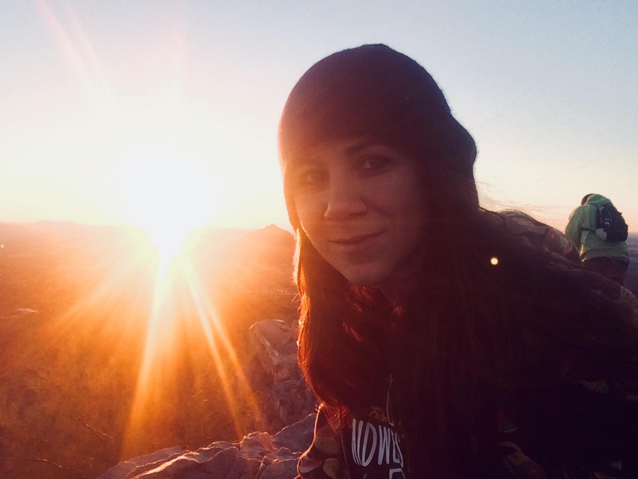 Kayla hiking a mountain at sunrise.
