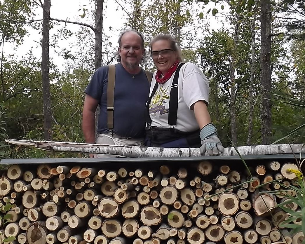 Jami and her husband Dan with wood harvested to heat their home.