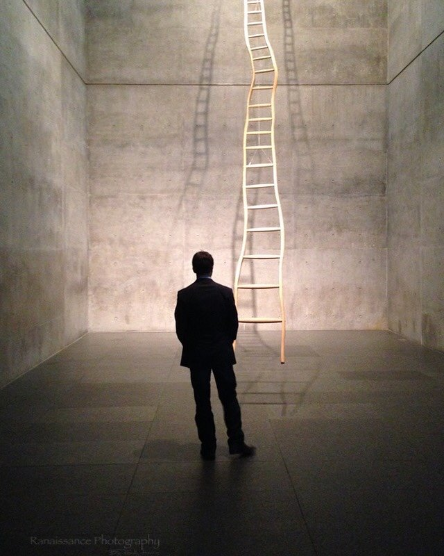 """My son and I was visiting the Kimball Art Museum one Sunday afternoon. As we approached this installation (the room with the ladder) I see this scene. This gentleman who was a another patron was standing observing the installation but it literally had the look like he had been placed there. In my eye the scene was just perfect.... I started fumble for my iPhone (5) which only had 1% of battery left. I came up shooting. As soon as I got of the first shot he moved. By the third shot my battery died. So I had no idea if I had the shot until we got back to the car over an hour later. I named it """"Corporate Ladder"""" the concrete, ladder to infinity and the guy in a suit pondering if it's worth it..... I was able to take art and turn it into new art...... on a cell phone. - Randy Harris"""