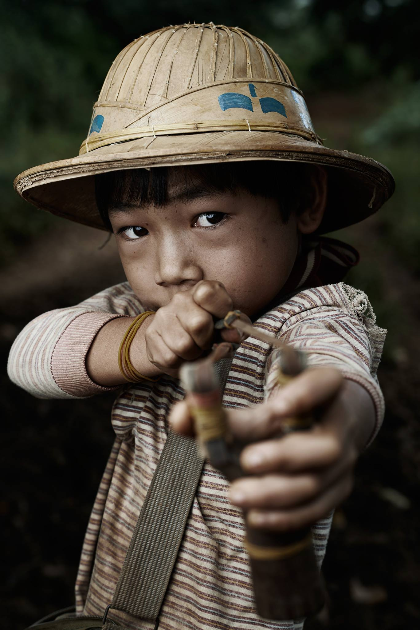 """This 8 years old burmese guy is a """"bird hunter"""". I had the opportunity to met him in my last trip to Burma in a remote region of the country. My guide was the translator. The guy explained us that he spend his life hunting birds in the morning to have something to eat every day. His parents consider a waste of time to send him to the school because he will not need that knowledge in his country in the future. - Victor Gonzalo"""