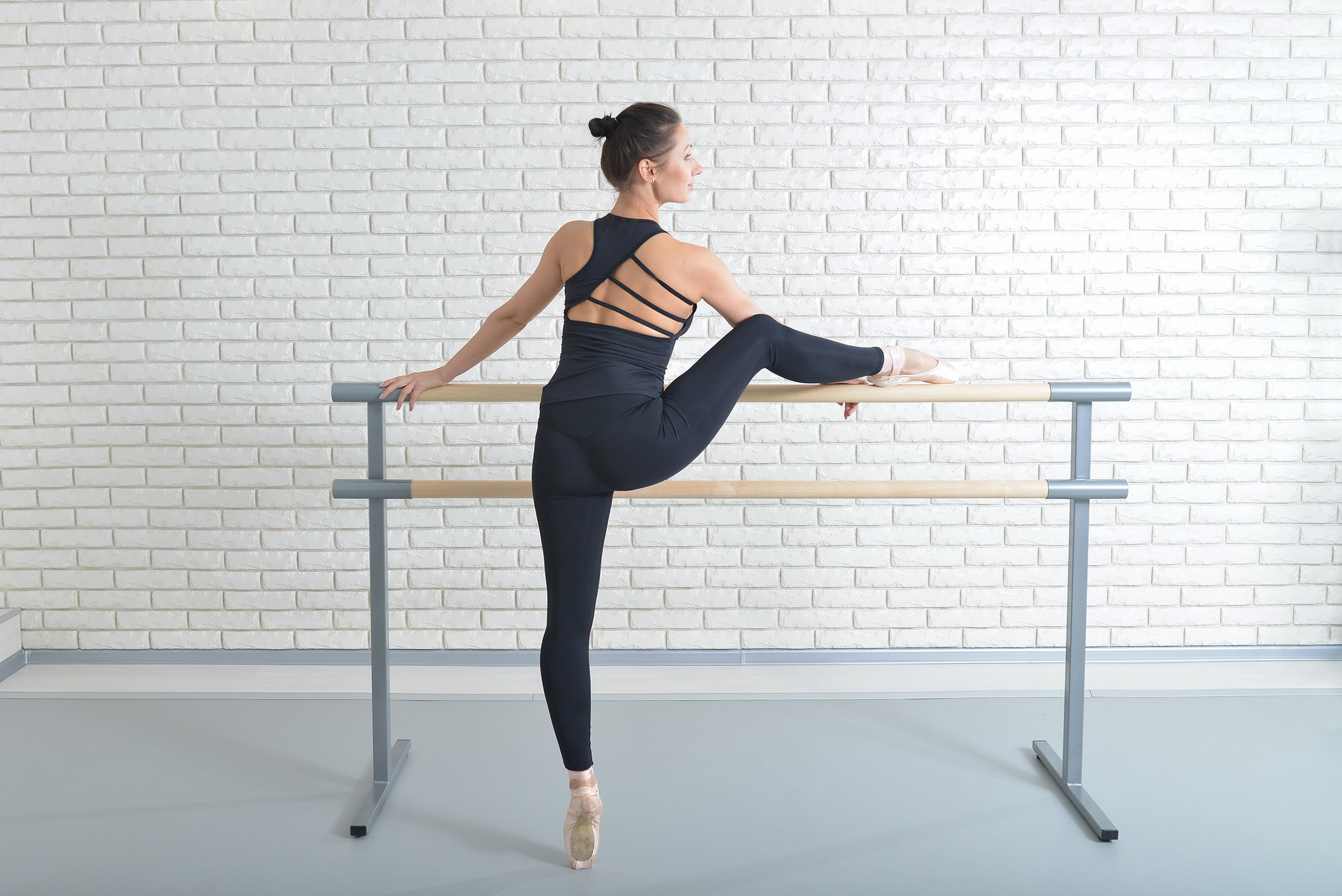 Ballerina-stretches-herself-near-barre-at-ballet-studio,-full-length-portrait.-863913310_3000x2003.jpeg