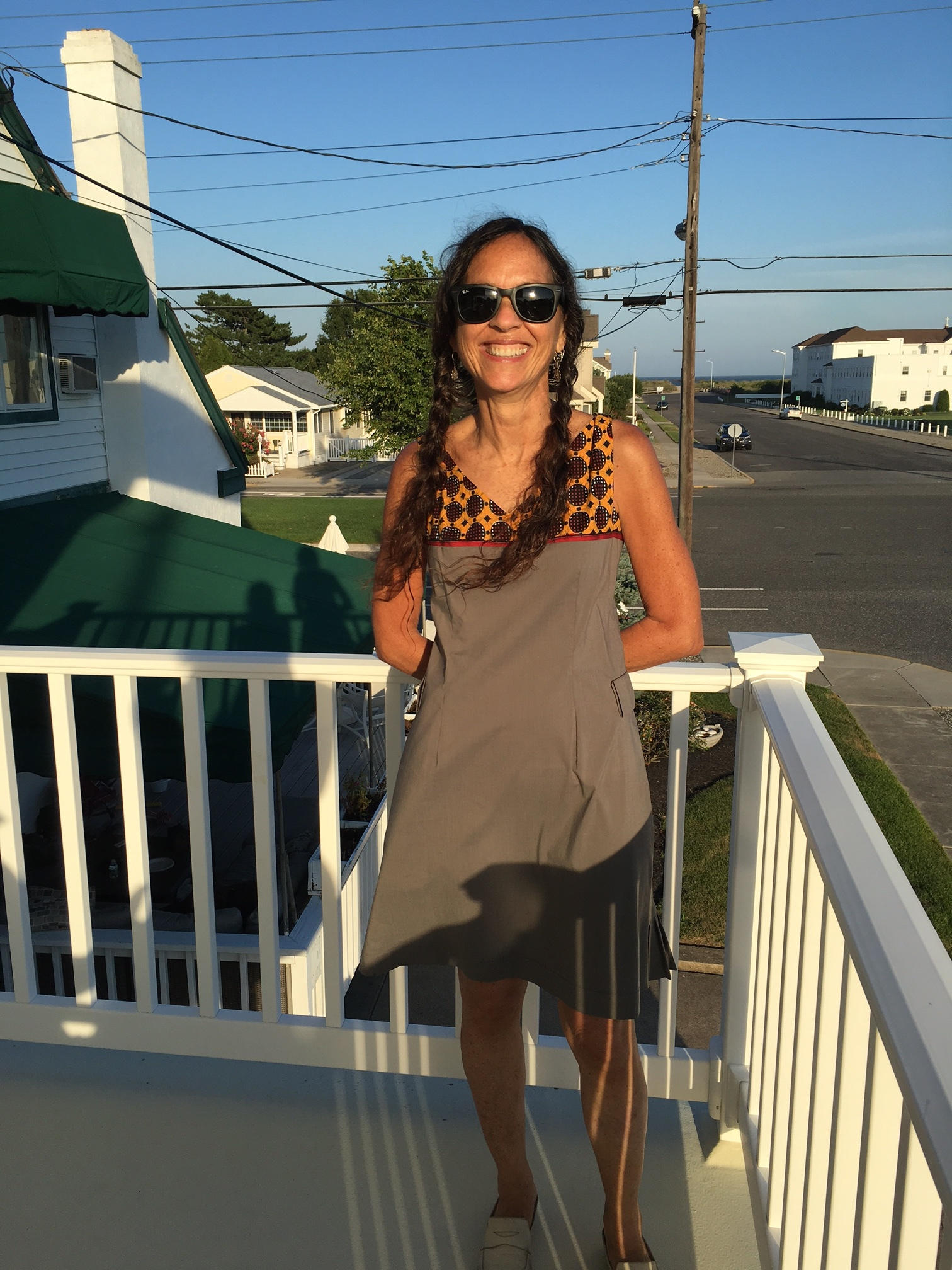 Jill is wearing a grey cotton A-line dress with an African print bodice and red selvage details at the Jersey shore.  the dress also has side pleats which are not visible in the photo.  really no accessories needed except a great pair of sunglasses and shoes.