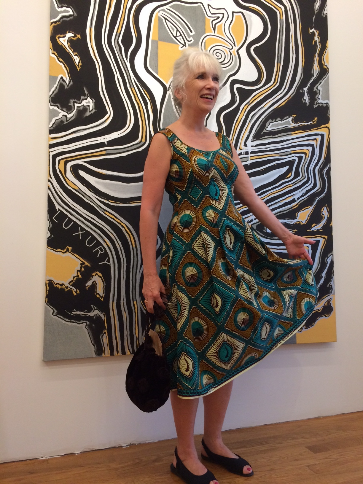 Devin Dougherty in Elizabeth Cannon Wax-print dress in front of Josh Abelow painting  photo: Taro Suzuki