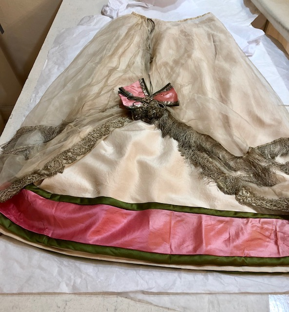 I replaced underskirt with tea-dyed silk tafetta, repaired torn net overskirt with silk crepeline and added original silk band to underskirt