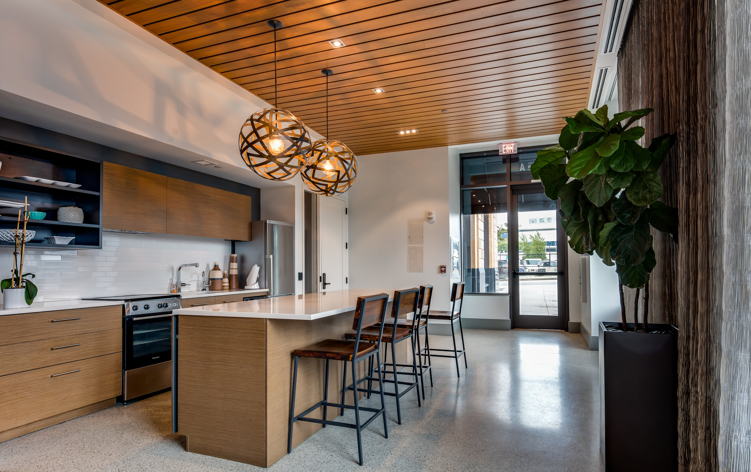 South Boston apartment building's entertaining space. I'm no designer, but this feels like a nice harmony between modern and natural, with a neat ceiling and light fixtures to help the transition. Those aren't curtains on the right - it's a natural wood wall.