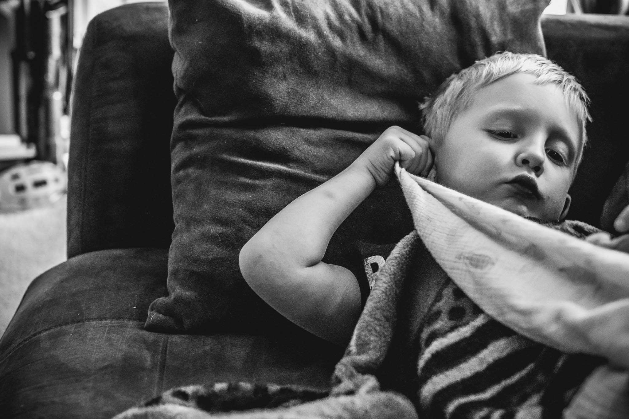 Totally not the perfect image. But the details here are what matter to me. He was tired and he took his blankie (one of 5, as long as they are muslin fabric he doesn't care) and rubs it in and along his ear. It's his tell that he is exhausted. Since he could touch his ear that was his thing.