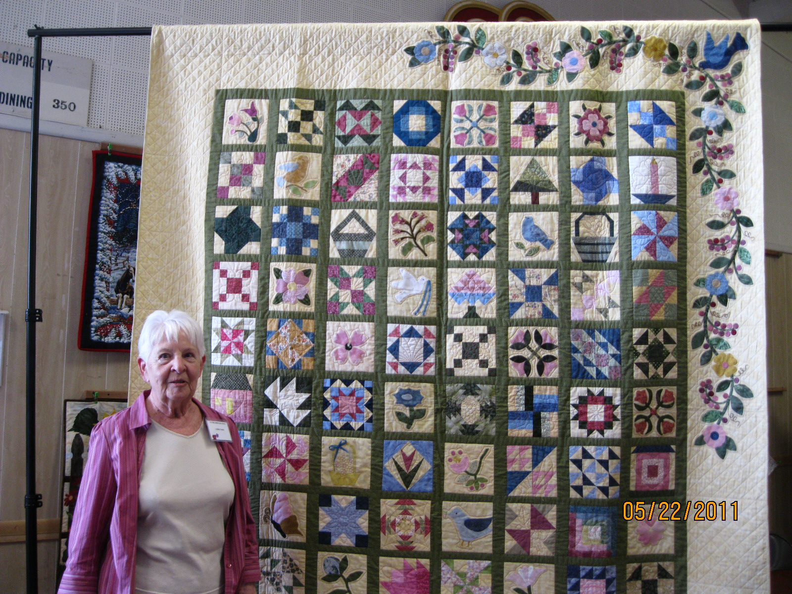 Flying Needles first Opportunity Quilt shown with the winner, and member, Linnie Faina, who won it.