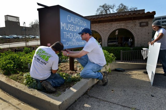 Jaime Garcias (from left), Mark Leaf and Josue Martinez install signs at the California Museum of Art site Thursday morning in Thousand Oaks.
