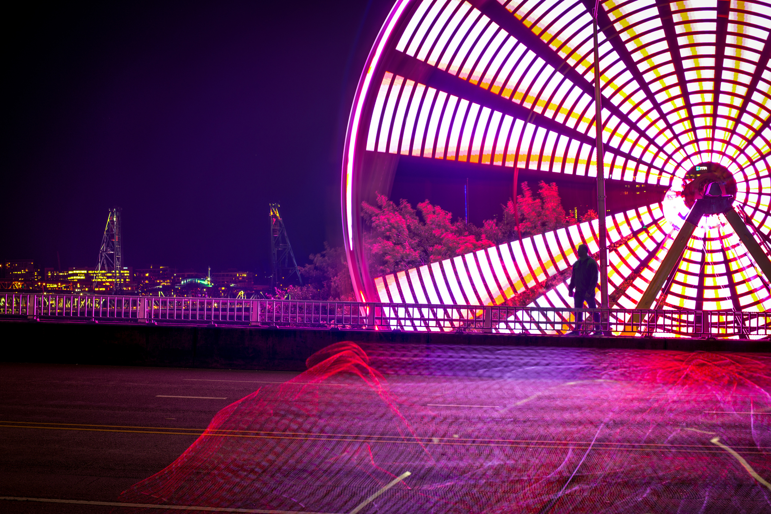 A man pauses in front of a Ferris Wheel on the Morrison st. bridge
