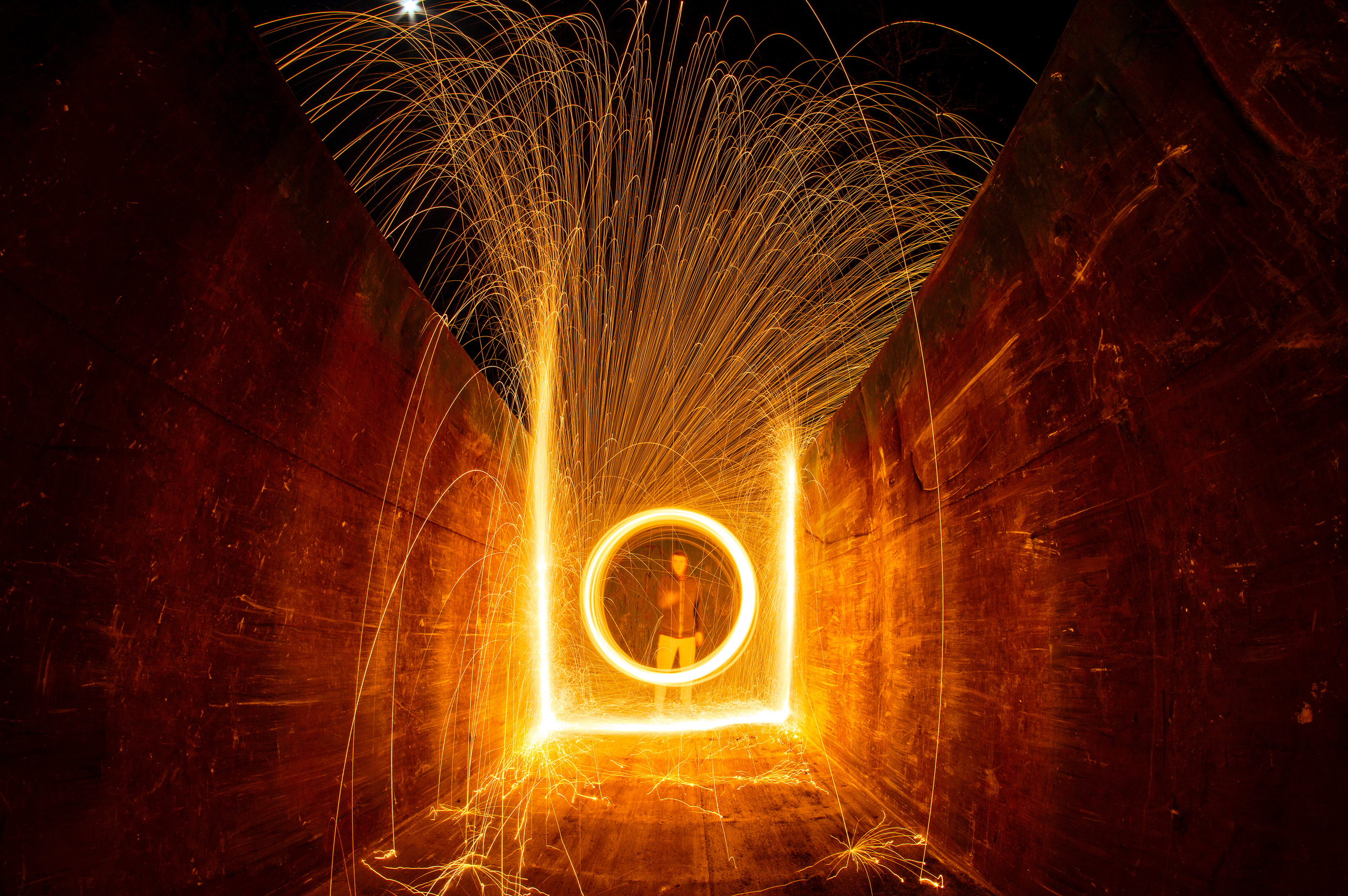 Swinging steel wool from an empty trash container on a construction site.