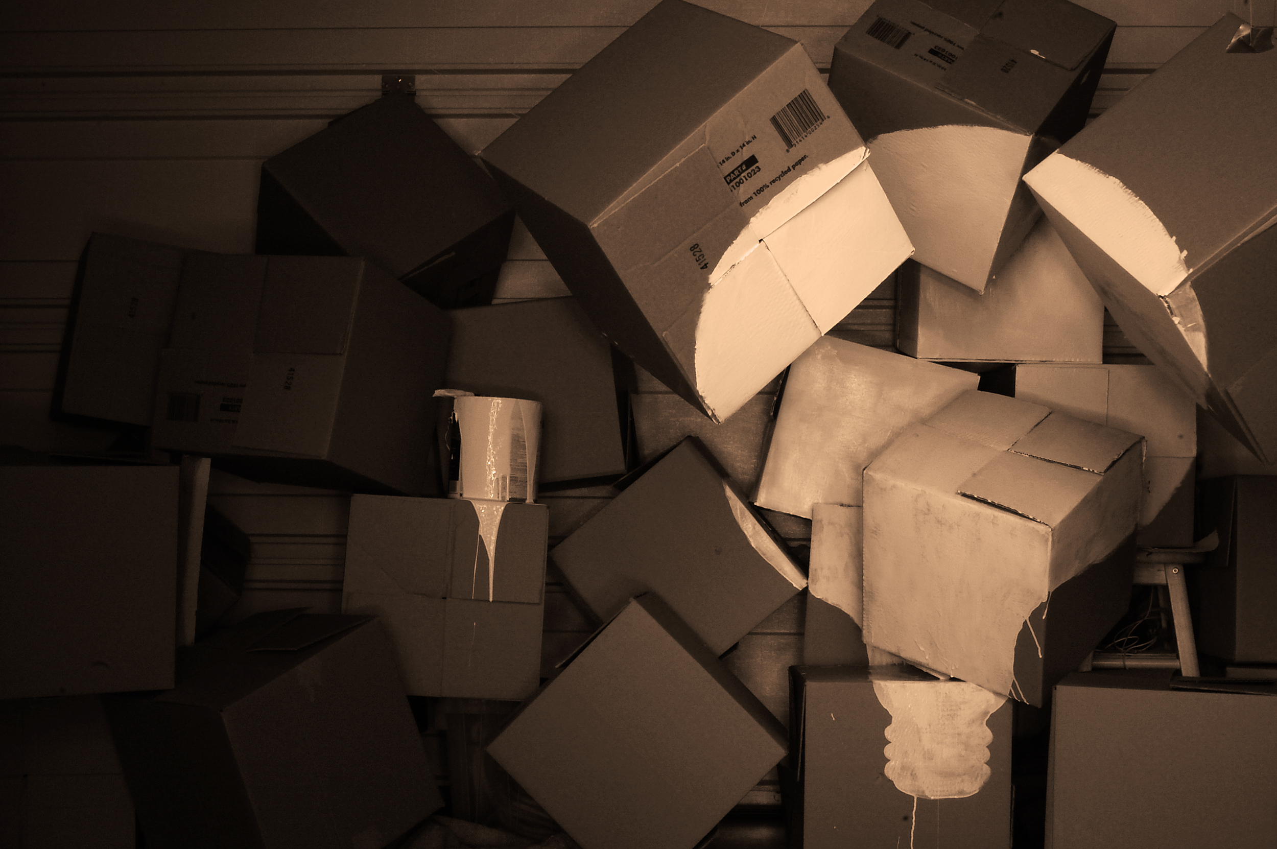 A lightbulbs' silhouette is painted on a pile of cardboard boxes