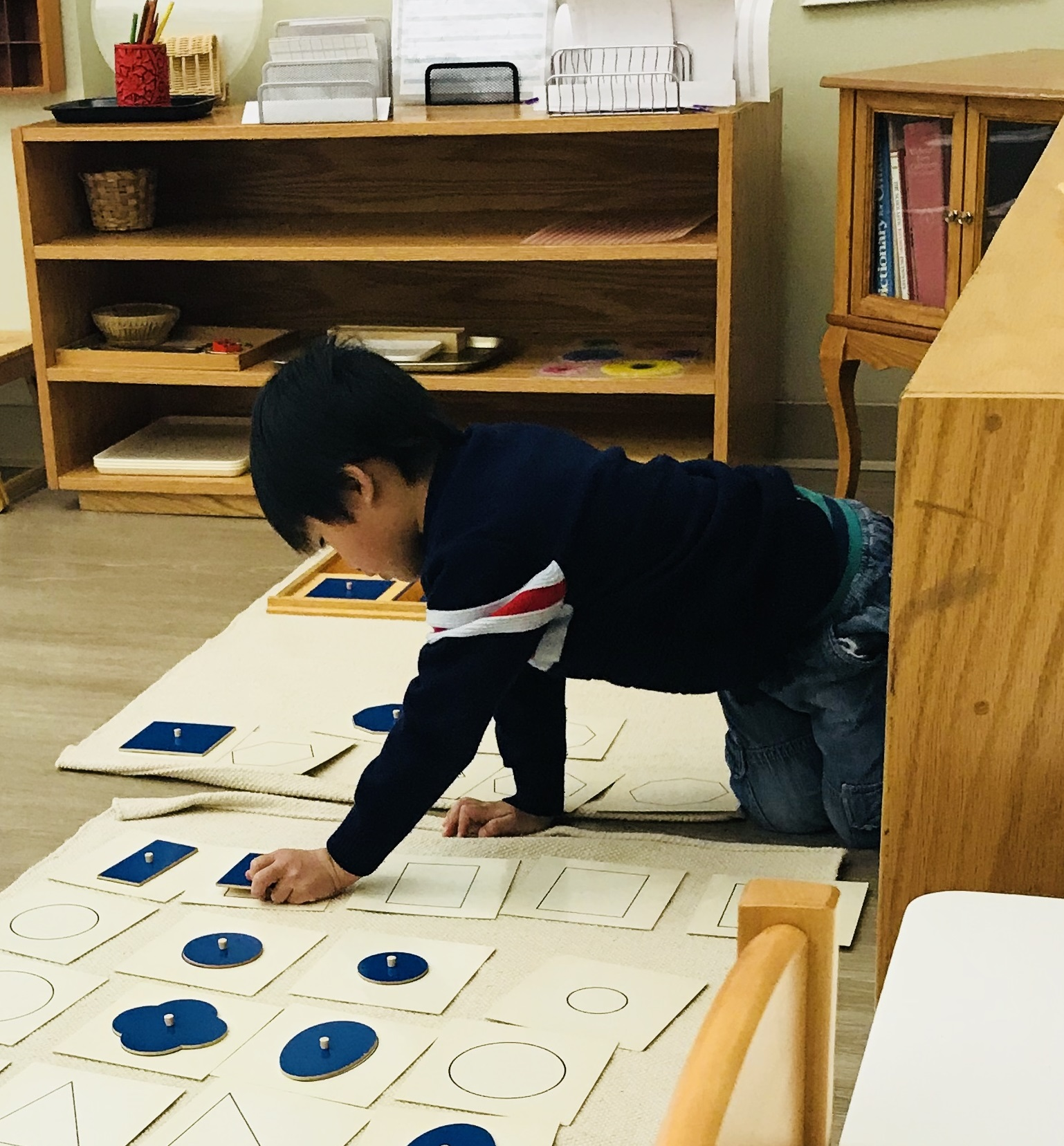 A picture of a child working with geometrical cabinet insets.