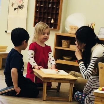 A teacher and a a boy are listening to a girl describing objects on the table.