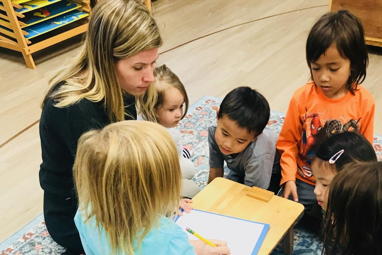 Teacher writing with children