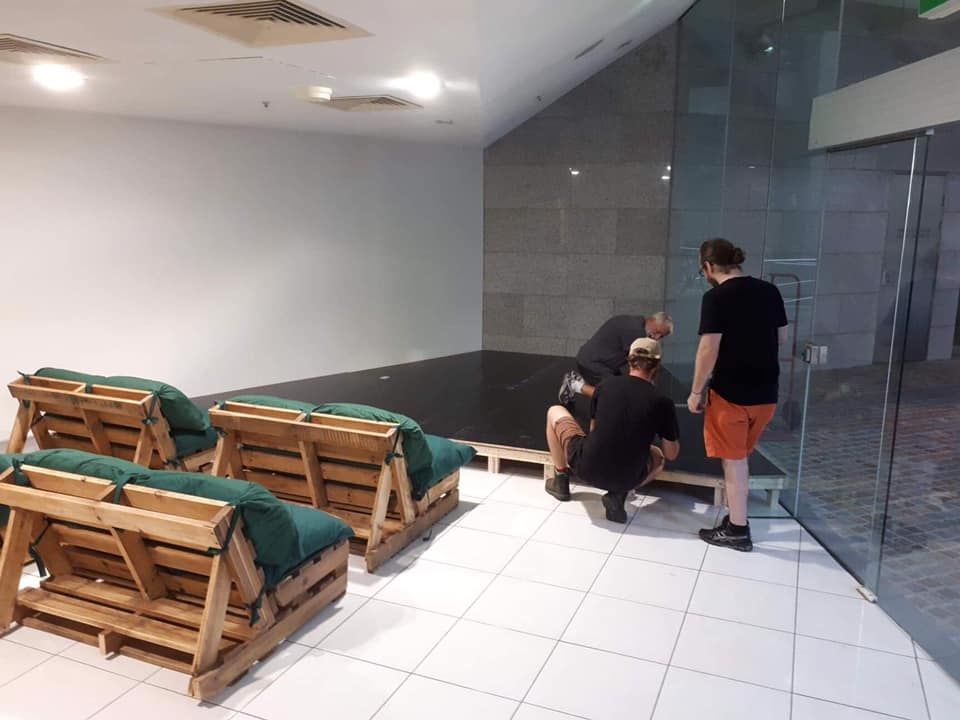 "First stage of the installation of stage and pallet chairs at ""the Glasshouse"" 33 Charlotte Street, CBD."