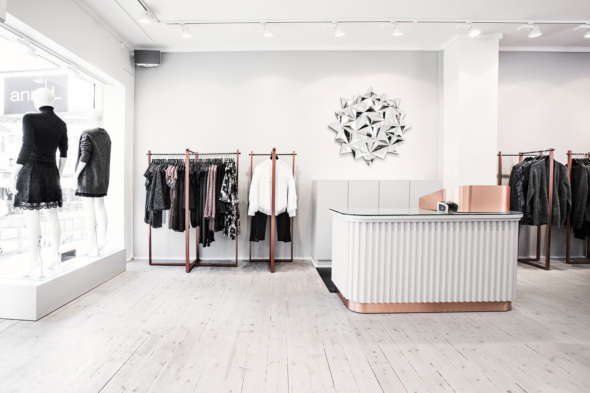 Shop Ann-L in Holbæk, Denmark. Weiße Elemente dominieren die Inneneinrichtung und persönlicher Raum erlauben dem Kunden durchzuatmen und erhöhen somit das positive Einkaufserlebnis.