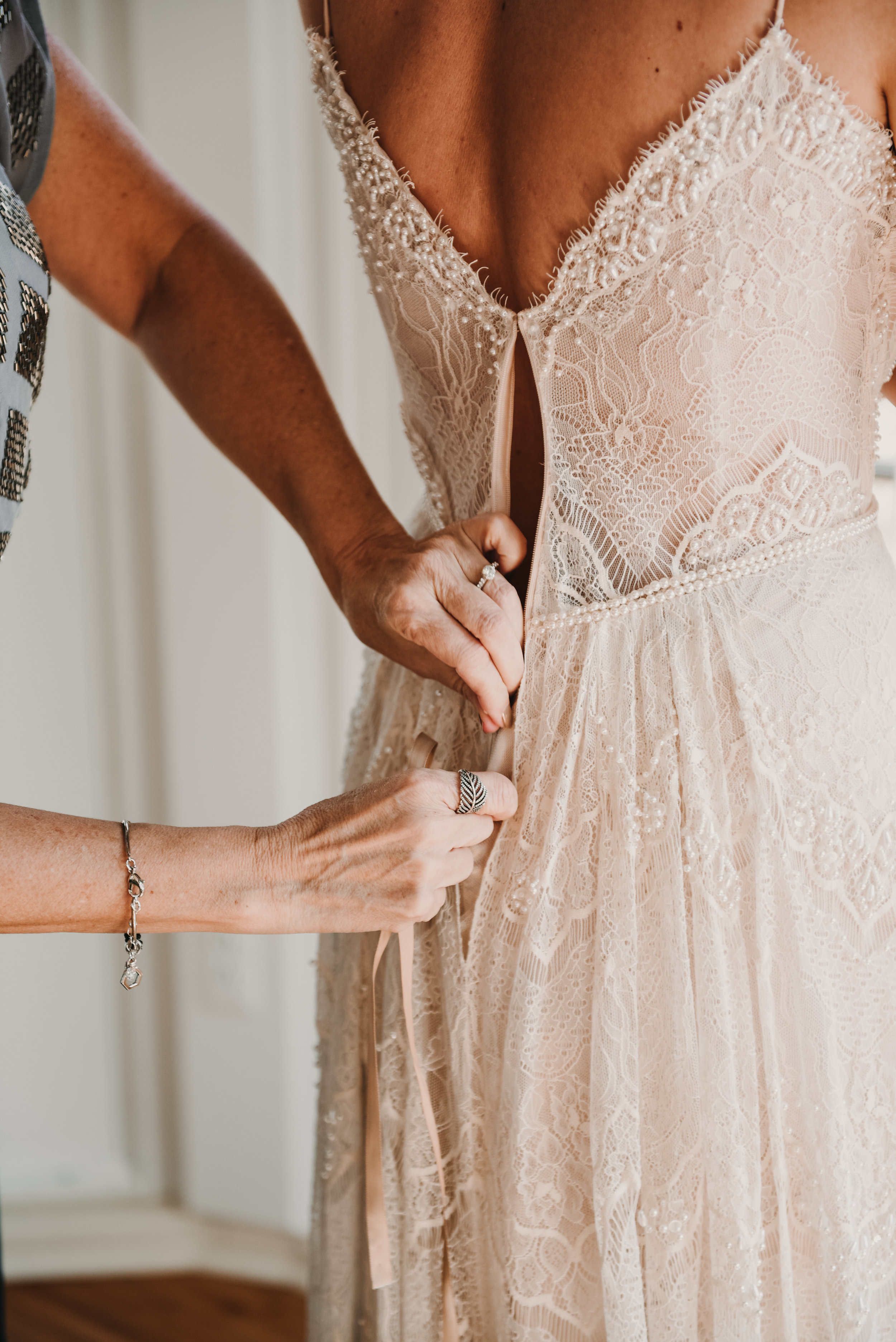 Mother of bride zipping up brides dress