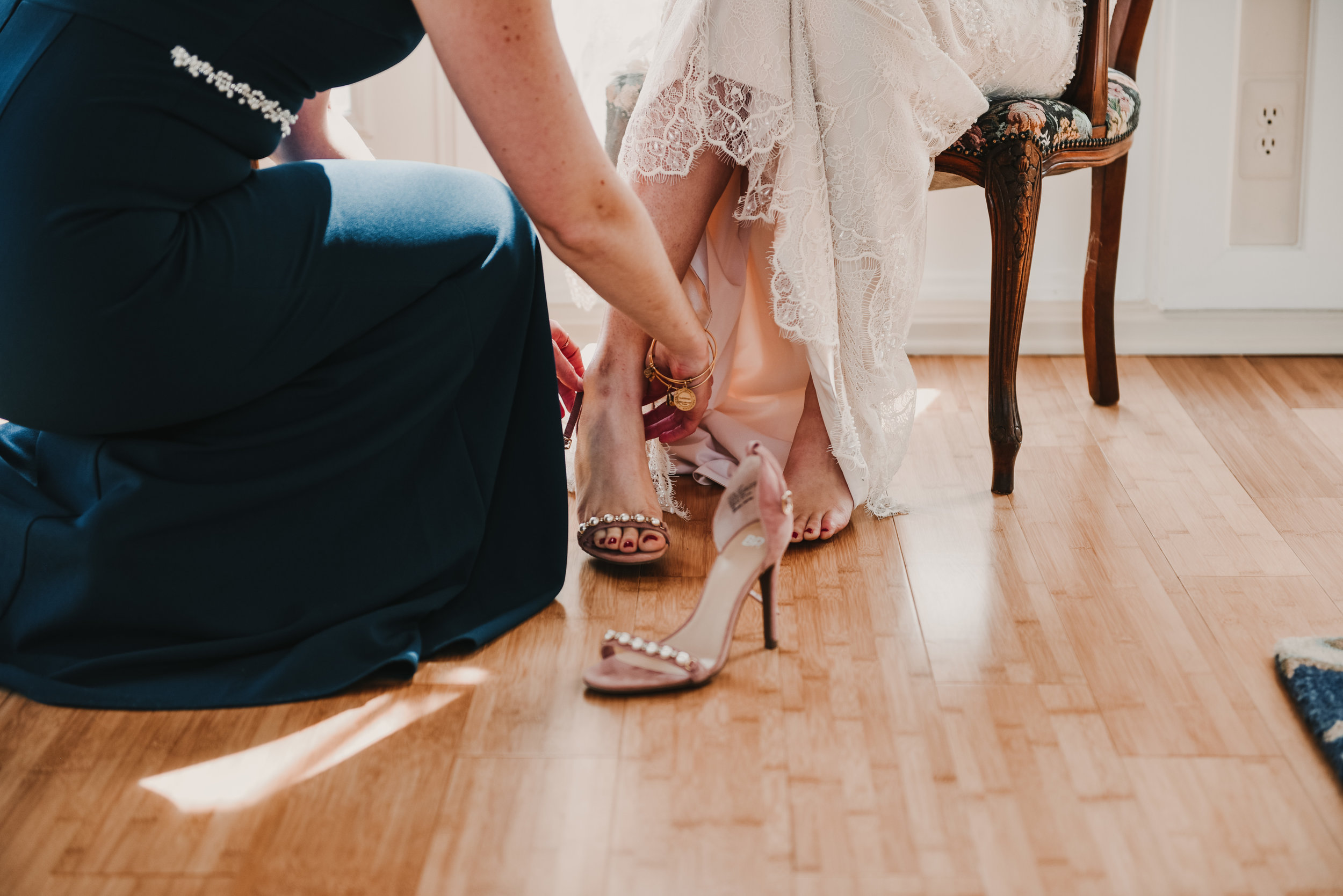Maid of honor putting on the brides shoes