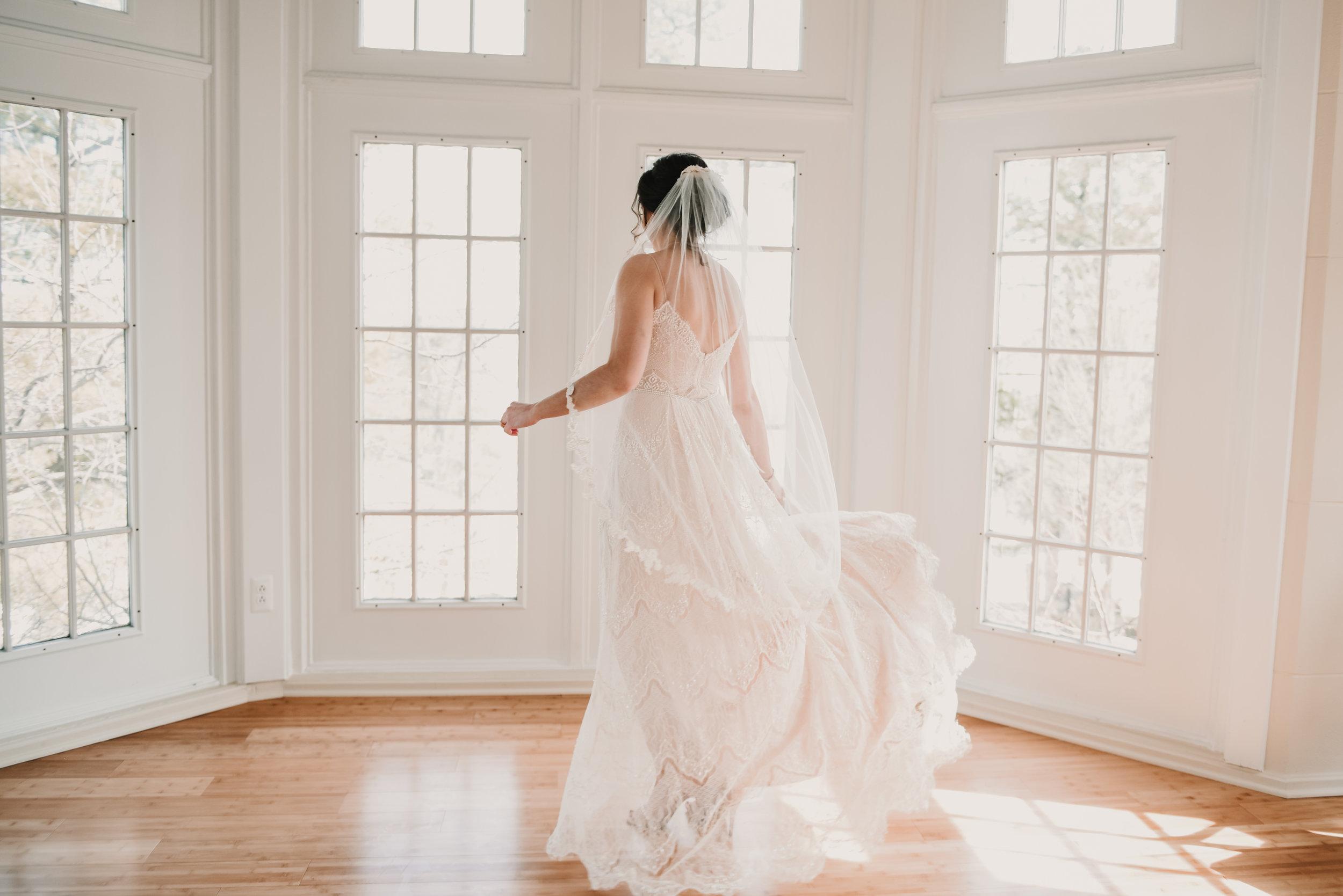 Bride dancing in her wedding dress by the window