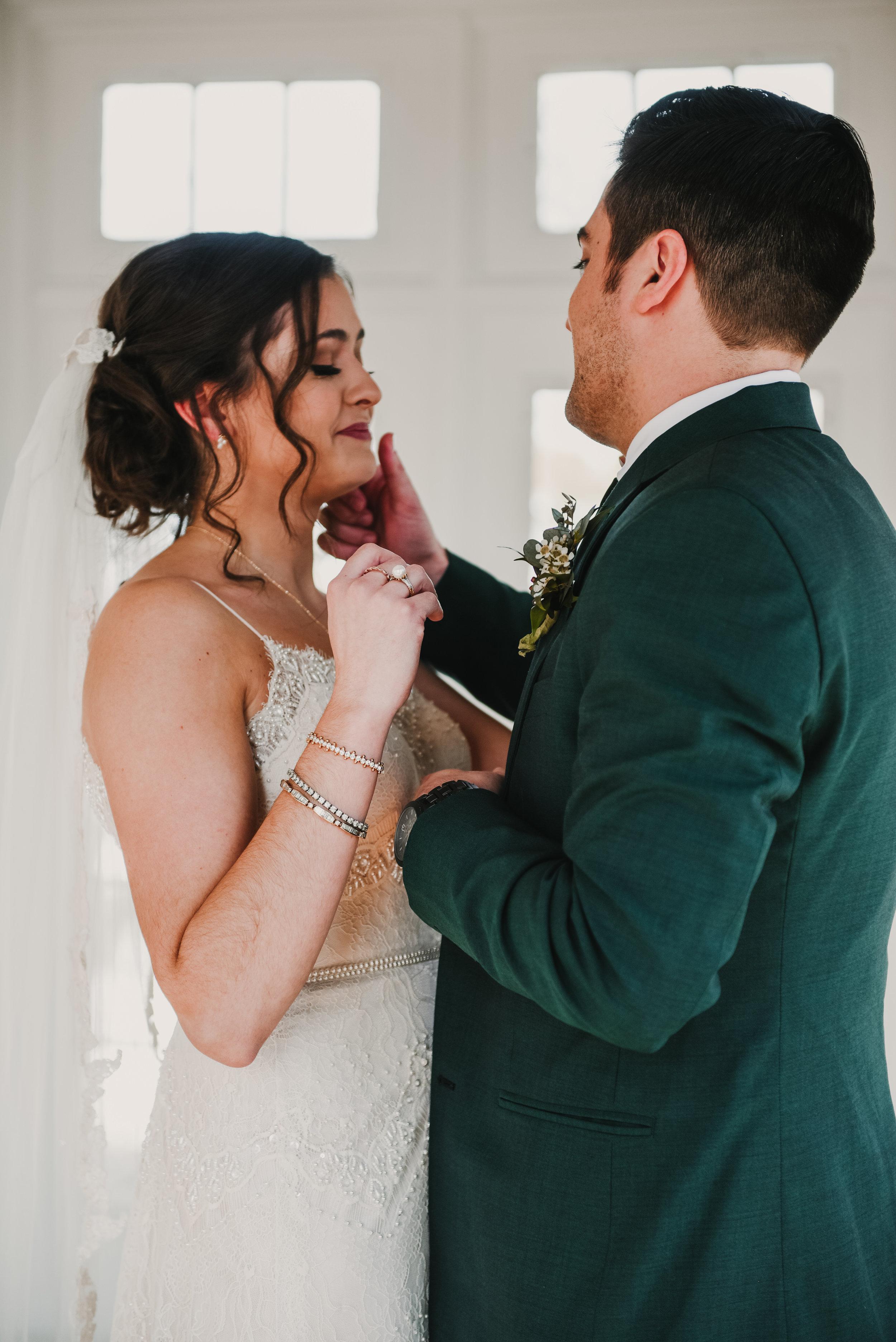 Groom wiping tear off of brides cheek
