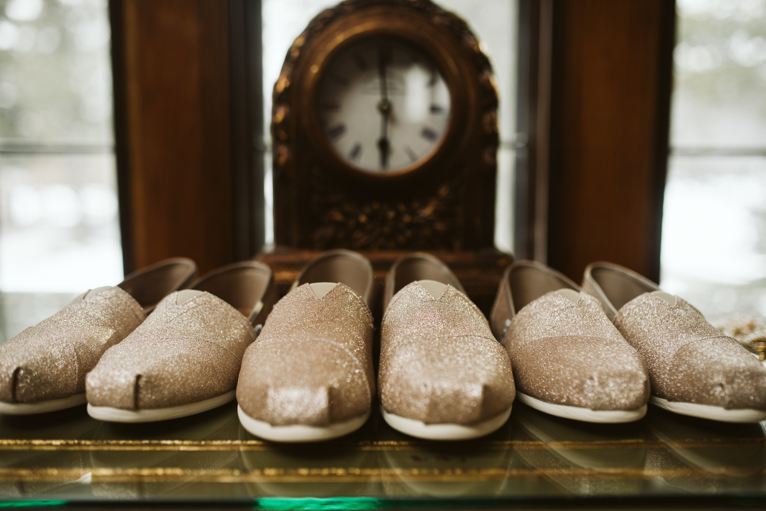 Brides and bridesmaid shoes in front of a clock
