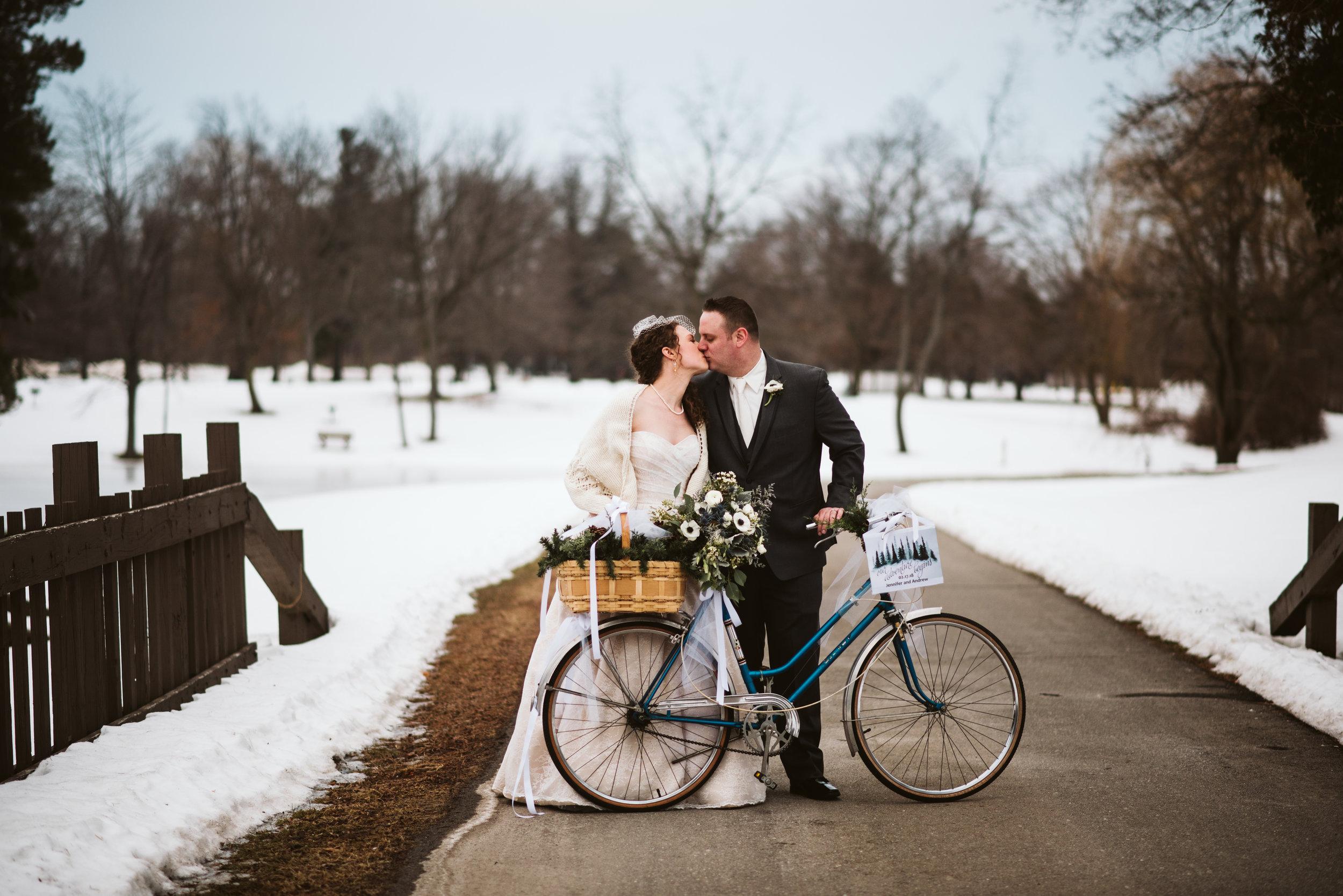 Bride and groom kissing  behind bicycle.