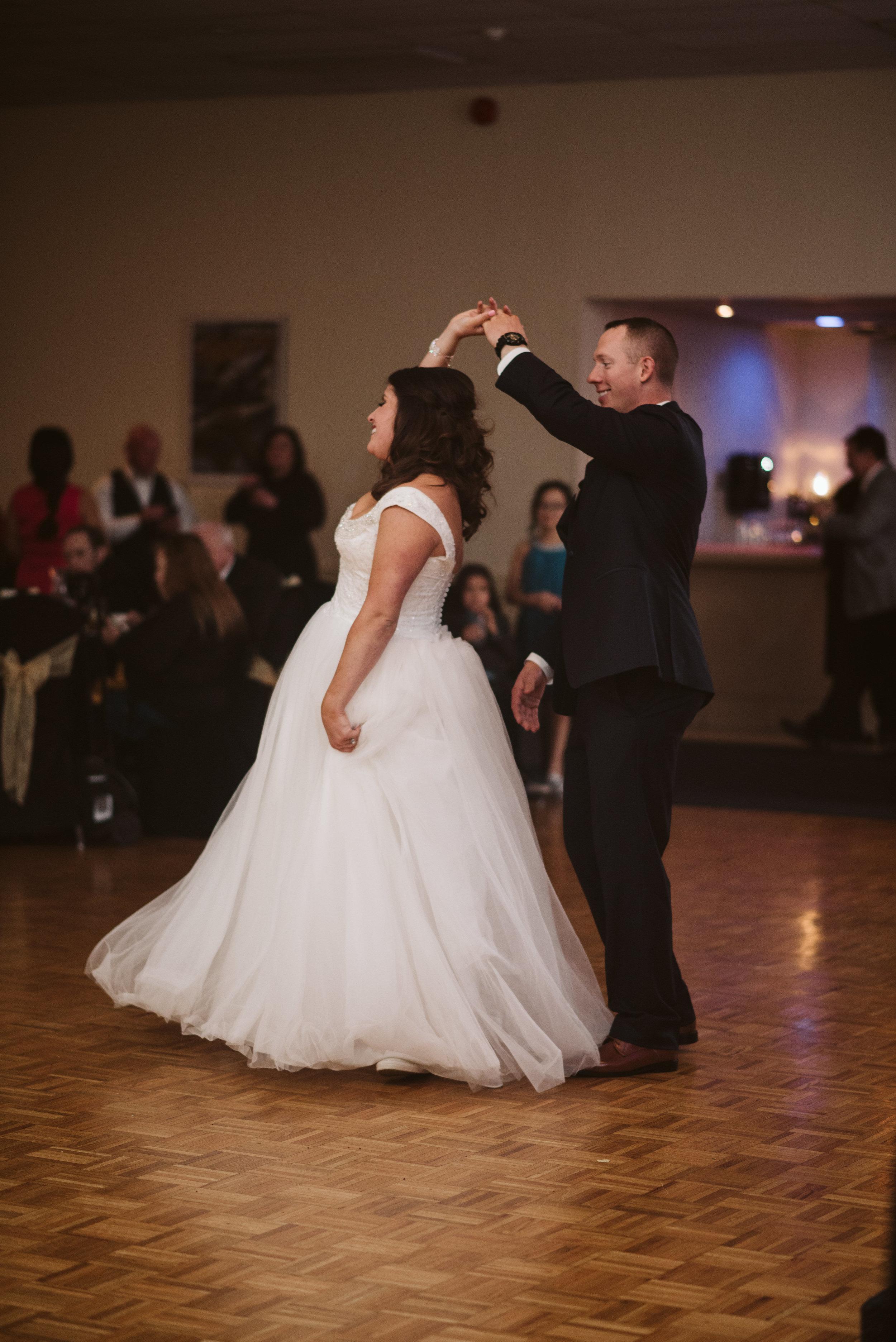 Groom twirls bride during first dance
