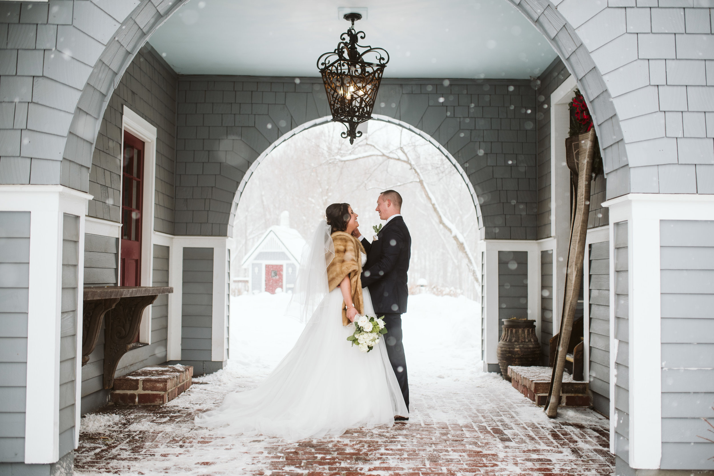Bride and groom under archway during snow storm