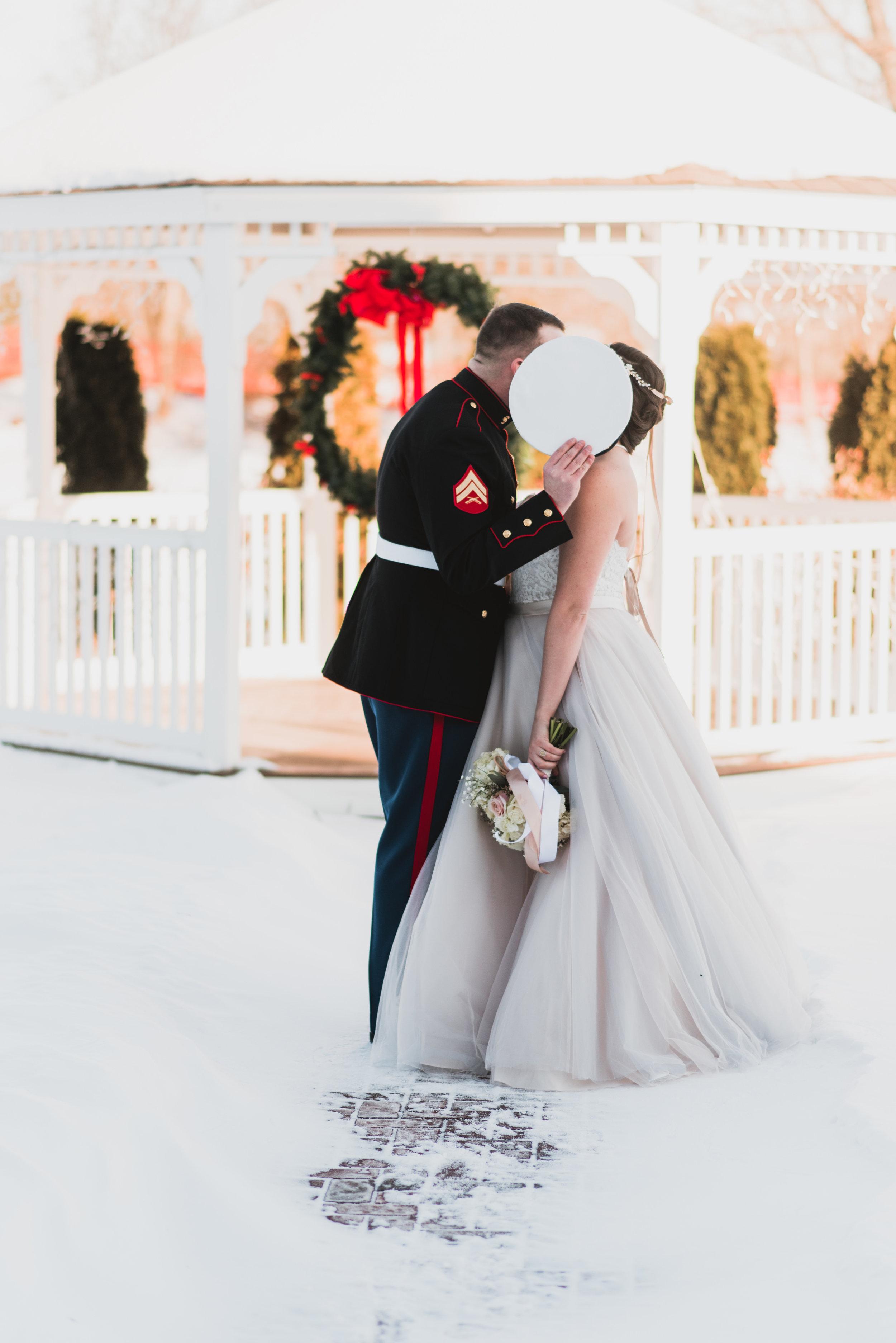 Brid eand groom kissing behind the hat