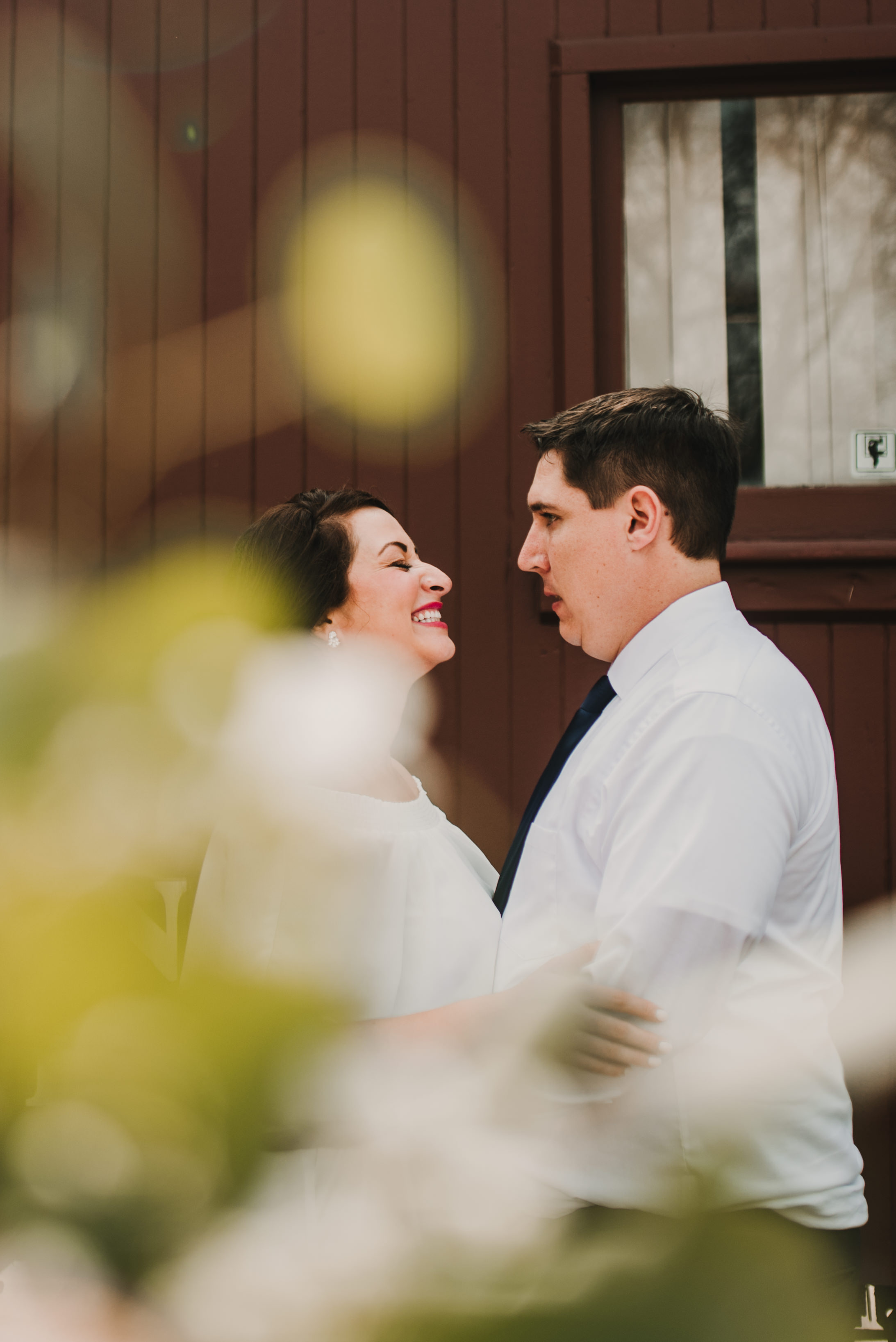 Bride and groom laughing together outside