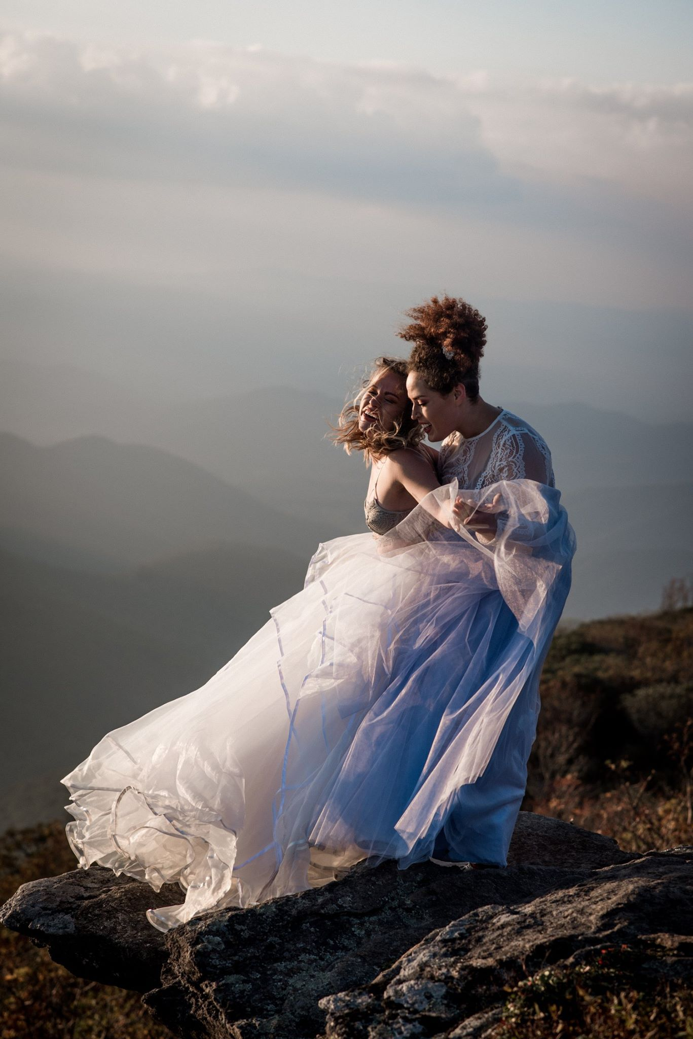 Bride and bride laughing during sunset on mountain