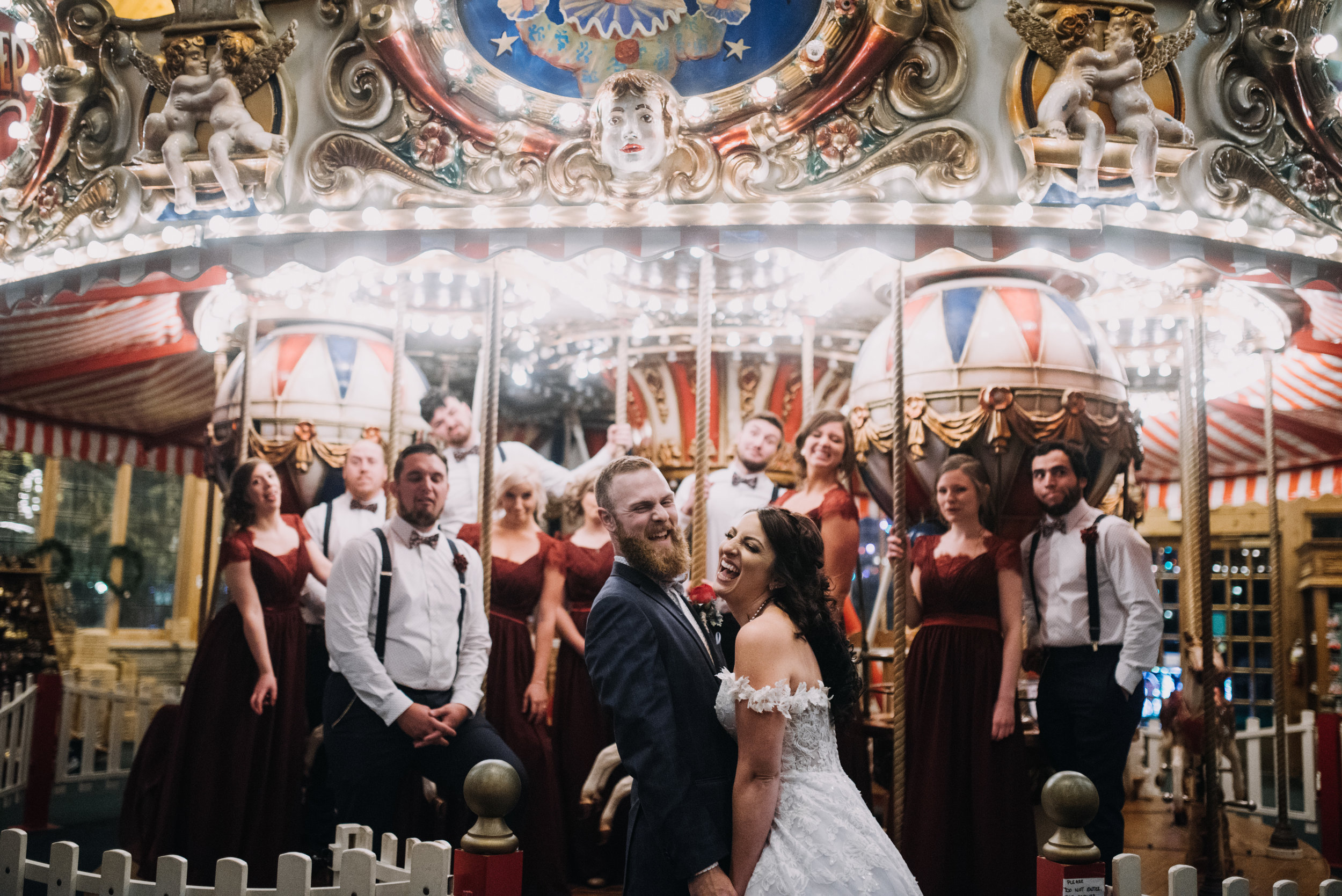 Bridal party laughing in front of a merry go round