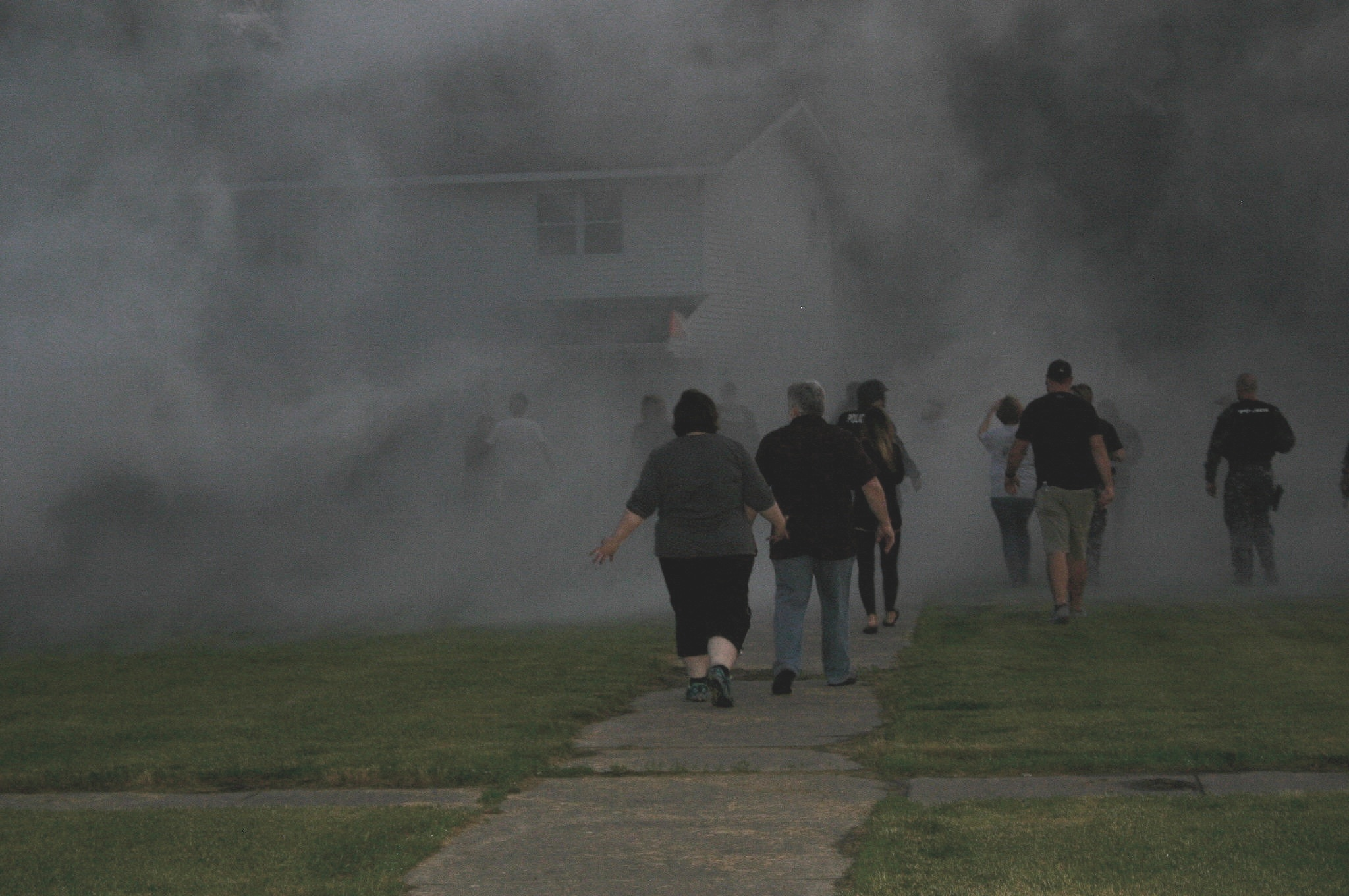 Participants walk into a cloud of smoke from one of SWAT's smoke canisters.