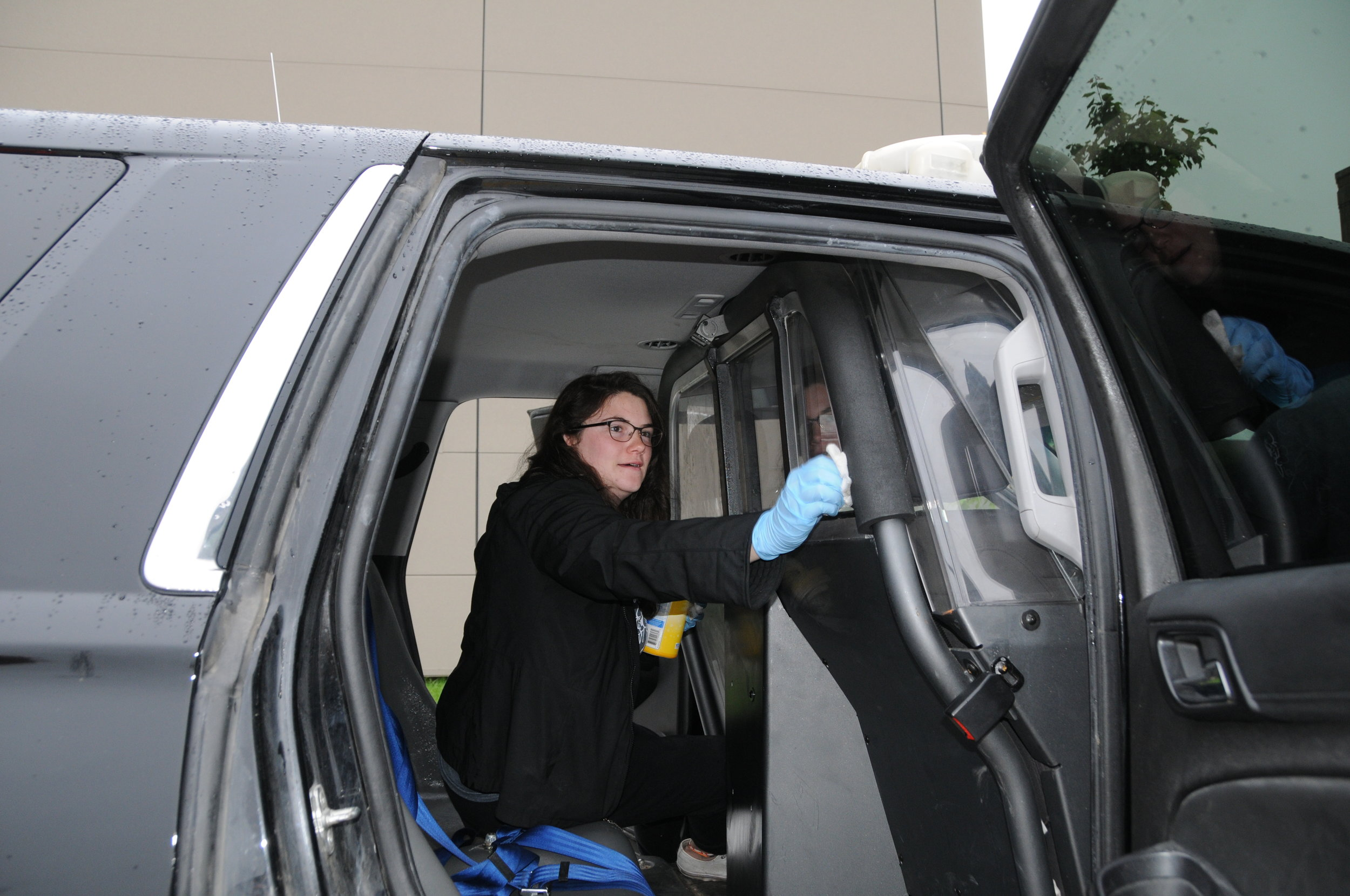 A student with Morninside College helps clean a marked patrol car at the department on Oct. 5 as part of Morningside Colleges Into the Streets volunteer project.